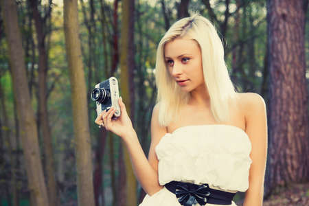 Beautiful adult girl with retro photo camera in a forest photo