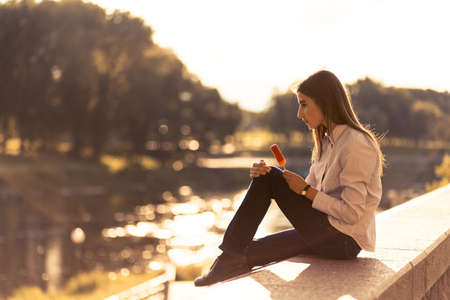 Beautiful young brunette girl sitting outdoors near the river photo