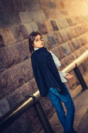 beautiful young girl hipster goes along a brick wall photo