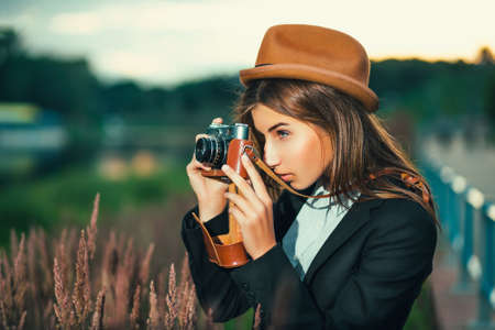 Beautiful hipster girl shooting with retro camera photo