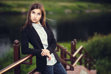 Beautiful young brunette girl standing alone outdoors photo