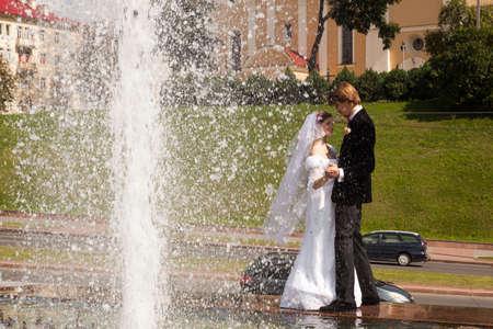 Beautiful bride and groom stand near fountain photo