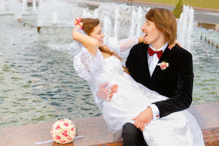 Bride and groom sitting together on the fountain photo