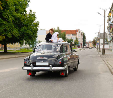 Romantic image of happy bride and groom in retro mobile