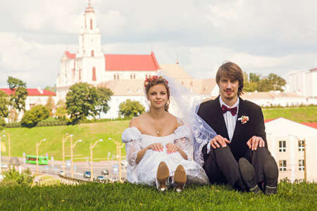newly-married couple sit on green grass in city photo