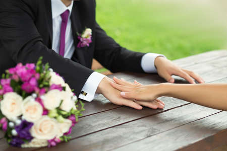 bride and groom holding hands on a table photo