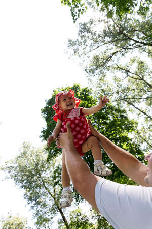 kinship: Father tossing up his daughter laughing in the park Stock Photo