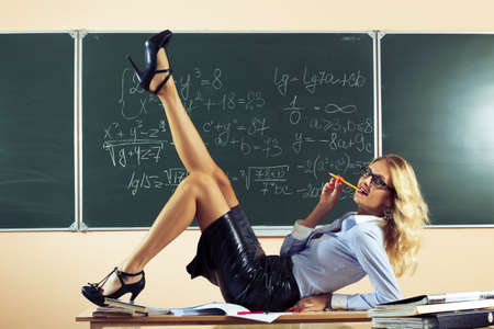 Beautiful young sexy teacher posing on table Stock Photo