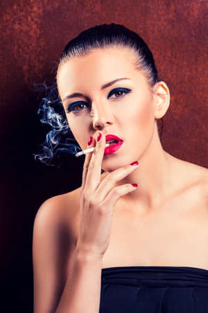 Close-up portrait of smoking girl with cigarette photo