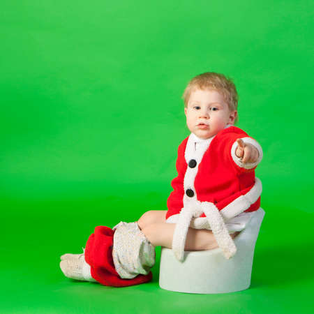 chamber pot: Boy in santa costume sitting on a chamber pot and pointing by finger Stock Photo