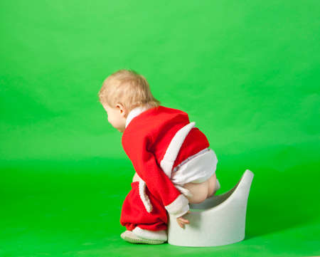 Boy in santa costume sitting on a chamber pot and pointing by finger photo