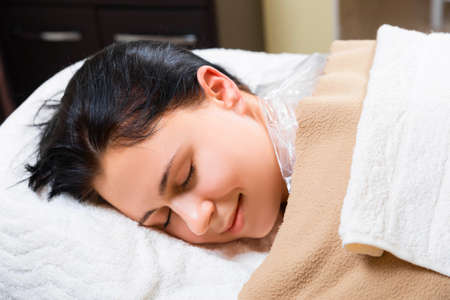 sleep well: young girl laying on massage table. white towel cover beautiful girl Stock Photo