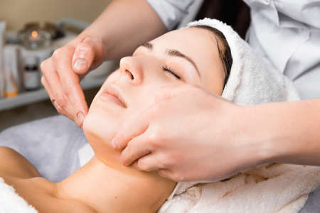skin care, medical beautician makes massage face after applying mask Stock Photo