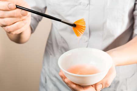 Beautician wet brush into the cream before applying photo