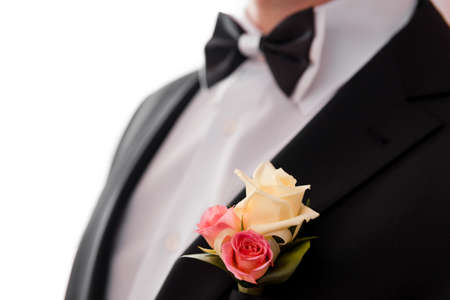 Boutonniere and bowtie close up. The grooms suit for the wedding ceremony photo