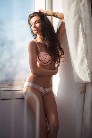 Sexy girl posing in underwear near the window photo