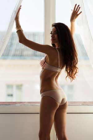 Sexy girl pushes to the side curtains photo
