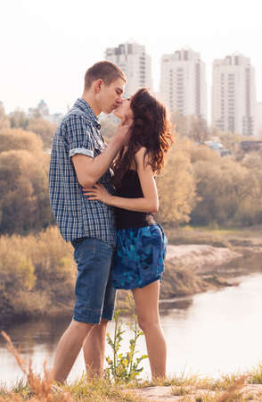 Beautiful young couple kissing on the coast photo