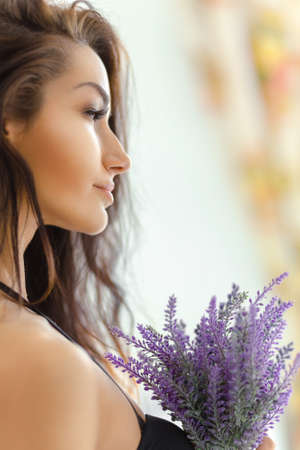 Portrait of young woman taking lavender. Isolated on white