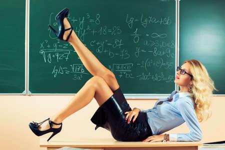 sexy teacher: Beautiful young sexy teacher posing on table Stock Photo
