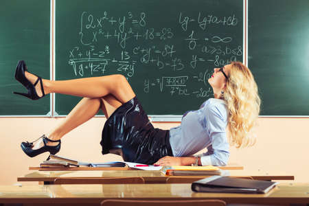 Beautiful young sexy teacher posing on table photo
