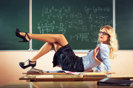 school girl sexy: Beautiful young sexy teacher posing on table Stock Photo
