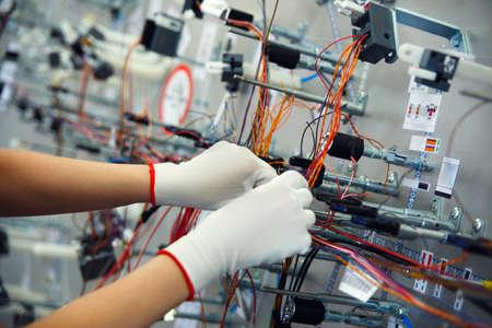 redes electricas: Las manos de los empleados que fabrican el cableado para el automóvil Foto de archivo