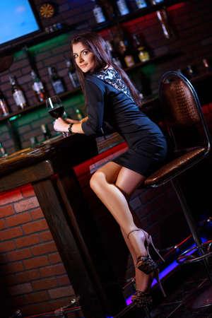 coziness: pretty woman in nightclub sitting alone have a glass of wine
