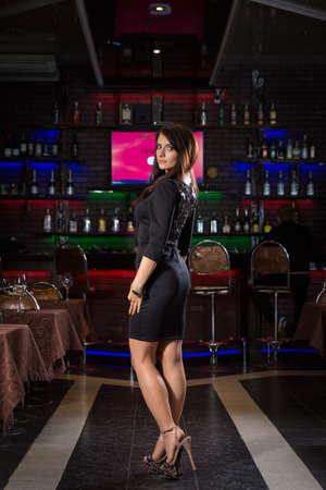 coziness: pretty young woman in nightclub standing alone Stock Photo