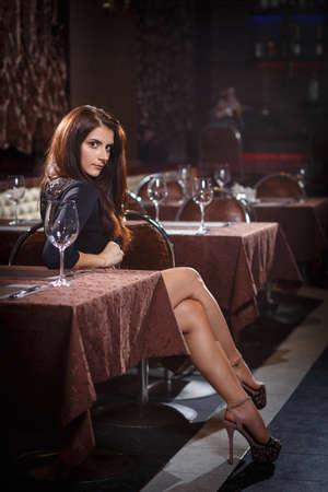 coziness: pretty woman in nightclub sitting alone at the table Stock Photo