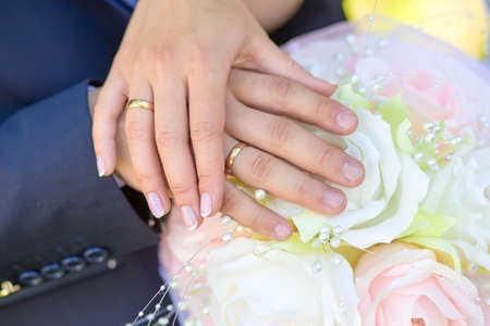 bride and groom holding hands with a bouquet photo