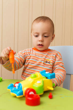 little boy repairs auto sitting on the table photo