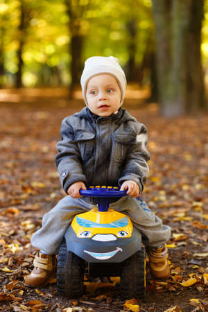 ��beautiful boy�: funny beautiful boy driving a car in the park Stock Photo