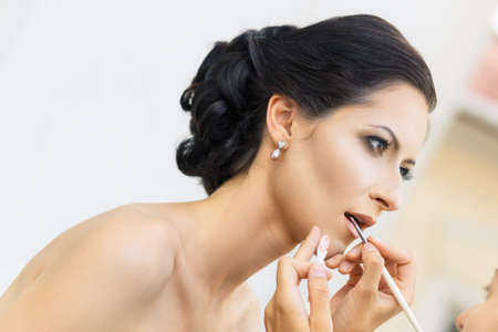 Stylist making up young beautiful bride before wedding