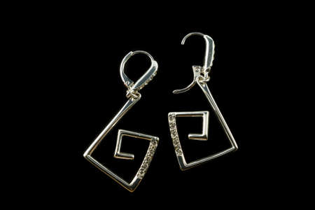 silver earrings with crystals isolated on a black background photo