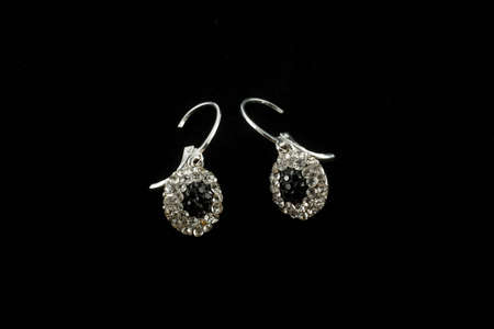 silver earrings with crystals on a black background photo