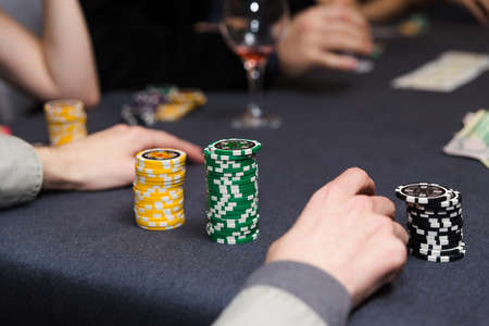 People playing poker. Players hands on table. photo