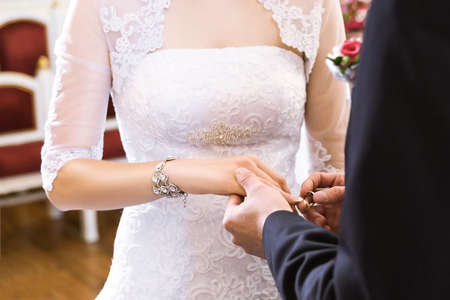 Hands with rings Groom putting golden ring on brides finger during wedding ceremony photo