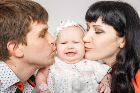3 persons: Young beautiful family of 3 persons Mum, Dad and little daughter posing in the studio