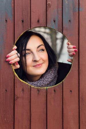 personas mirando: Modelo de moda bonita con el pelo negro mira a trav�s de la ventana Foto de archivo
