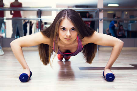 push: fitness woman working out doing push-ups strength training in the gym