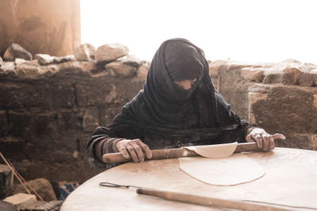 bedouin: Old Arab woman prepares bread in a Bedouin village Editorial