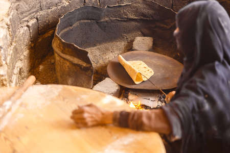 Old Arab woman prepares bread in a Bedouin village Stock Photo