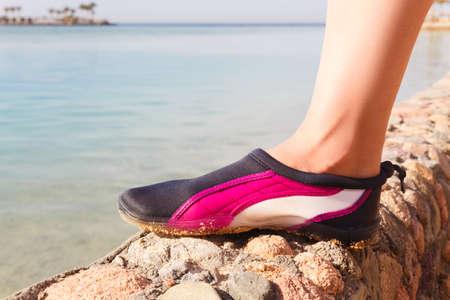 neoprene: Water shoes  swimming shoe in Pink neoprene on rocks in water on beach. Stock Photo