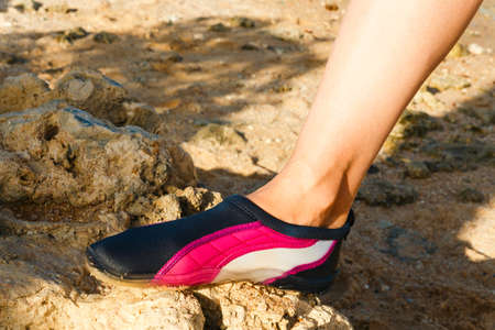 water shoes: Water shoes  swimming shoe in Pink neoprene on rocks in water on beach. Stock Photo