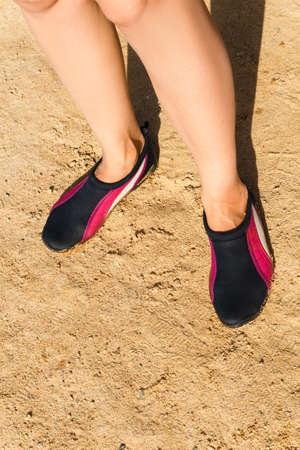 neoprene: Swimming neoprene shoes in water on beach.
