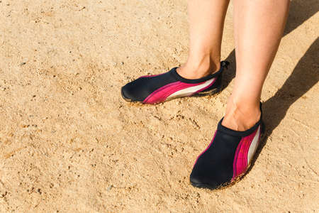 water shoes: Swimming neoprene shoes in water on beach.