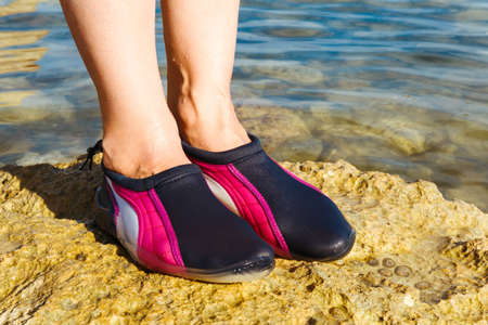 swimming shoes: Swimming neoprene shoes in water on beach.