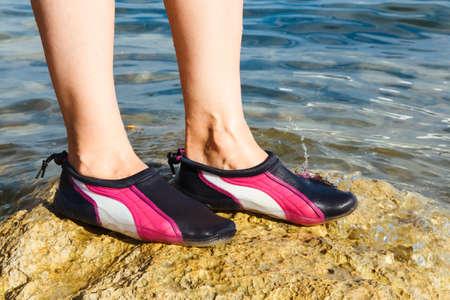 Swimming neoprene shoes in water on beach.