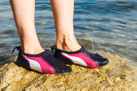 Swimming neoprene shoes in water on beach.